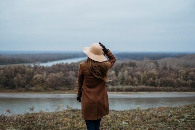 Widok Kobiety W Kapeluszu Z Tyłu, Podziwiając Widok Na Jezioro Darmowe Zdjęcia