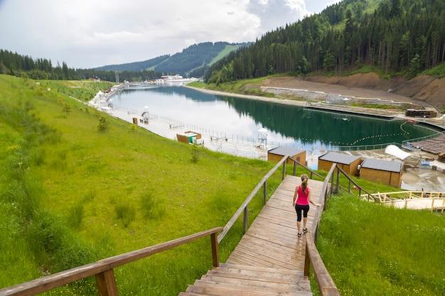 Widok Młodej Kobiety Sportive W Fitness Ubrania Z Tyłu Stojący Na Zewnątrz W Pobliżu Dużego Jeziora W Górach Z Widokiem Na Przyrodę. Premium Zdjęcia