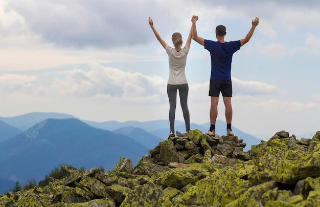 Widok Młodej Pary, Wysportowanego Chłopca I Szczupłej Dziewczyny Stojącej Z Uniesionymi Rękami Na Szczycie Góry Skalistej, Cieszący Się Zapierającym Dech W Piersiach Widokiem Na Góry Latem. Koncepcja Turystyki, Sukcesu I Zdrowego Stylu życia. Premium Zdjęcia