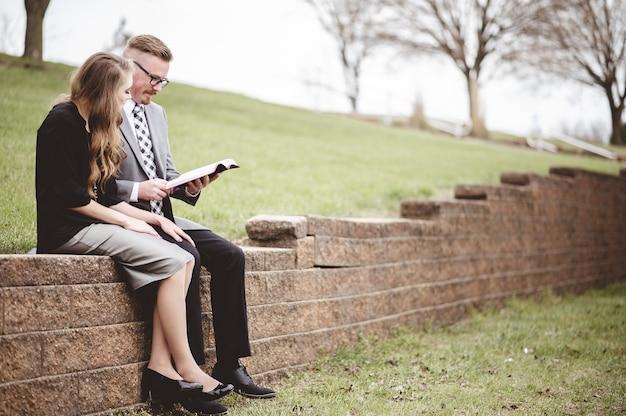 Widok Na Kilka Ubrań Formalnych Podczas Wspólnego Czytania Książki W Ogrodzie Darmowe Zdjęcia