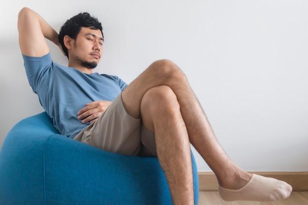 Widok Na Nogi Mężczyzny Na Białym łóżku Z Telewizorem I Rośliną. Premium Zdjęcia