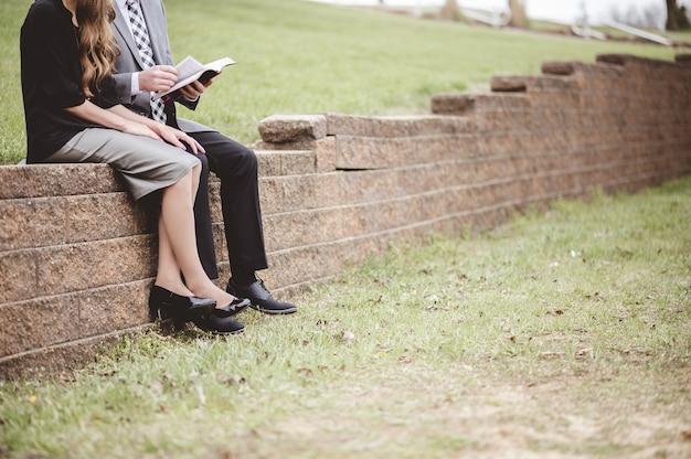 Widok Na Parę Ubrań Formalnych I Czytając Książkę Siedząc W Ogrodzie Darmowe Zdjęcia