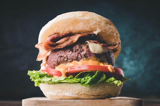 Widok Na świeży Smaczny Burger Na Drewnianym Stole. Hamburger Z Boczkiem, Serem, Sałatą, Pomidorem I Sosem Premium Zdjęcia