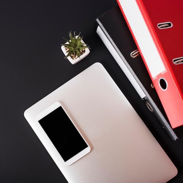 Widok Ogólny Telefonu Komórkowego Na Laptopie; Soczyste Rośliny I Pliki Papierowe Na Czarnym Tle Darmowe Zdjęcia