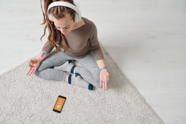 Widok Pogodnej Młodej Kobiety W Słuchawkach Siedzącej W Pozie Lotosu I Słuchania Muzyki Do Medytacji Premium Zdjęcia