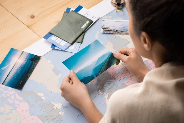 Widok Przez Ramię Kobiety Siedzącej Na Stole Z Mapą świata I Marzącej O Podróży Oglądającej Zdjęcia Premium Zdjęcia