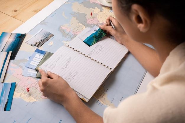 Widok Przez Ramię Turysty Sprawdzającego Notatki W Dzienniku Podczas Planowania Miejsc Do Odwiedzenia Oglądając Zdjęcia Premium Zdjęcia
