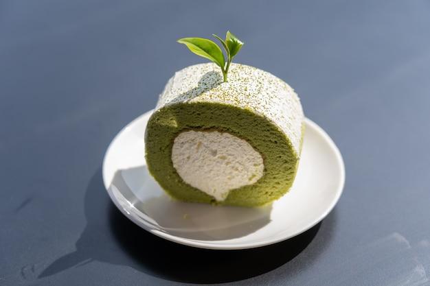 Widok rolki ciasta zielonej herbaty umieścić na drewnianym stole. Premium Zdjęcia
