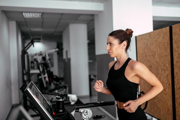 Widok z boku atrakcyjna kobieta sportowe działa na bieżni. Premium Zdjęcia