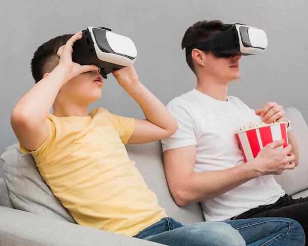 Widok Z Boku Chłopca I Mężczyzny Oglądania Filmu Za Pomocą Zestawu Słuchawkowego Rzeczywistości Wirtualnej Darmowe Zdjęcia