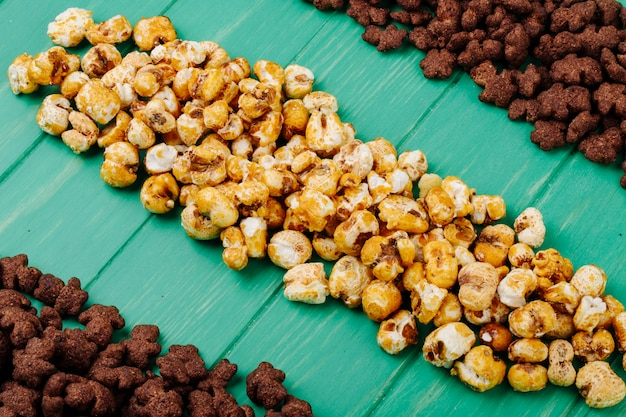 Widok Z Boku Chrupiące Czekoladowe Płatki Kukurydziane I Popcorn Karmelowy Na Zielonym Tle Drewnianych Darmowe Zdjęcia