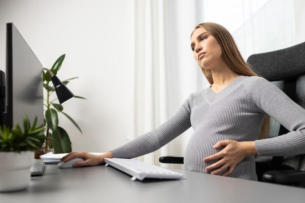 Widok Z Boku Ciężarnej Bizneswoman Na Jej Biurku, Trzymając Jej Brzuch Darmowe Zdjęcia