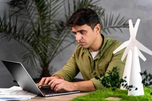 Widok Z Boku Człowieka Pracującego Nad Projektem Ekologicznej Energii Wiatrowej Z Laptopem Darmowe Zdjęcia