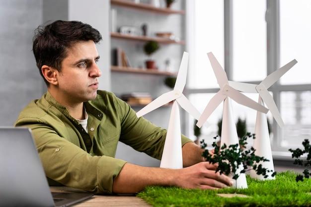 Widok Z Boku Człowieka Pracującego Nad Projektem Ekologicznej Energii Wiatrowej Darmowe Zdjęcia