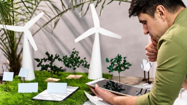 Widok Z Boku Człowieka Za Pomocą Tabletu Obok Ekologicznego Układu Projektu Energii Wiatrowej Darmowe Zdjęcia