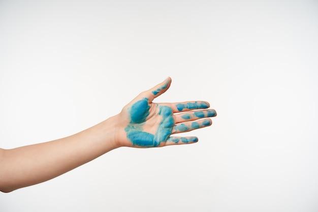 Widok Z Boku Dłoni Kobiety Z Niebieskim Kolorem, Która Jest Podniesiona Podczas Uścisku Czyjejś Dłoni, Rozkładając Ją Do Przodu Podczas Pozowania Na Biało Darmowe Zdjęcia