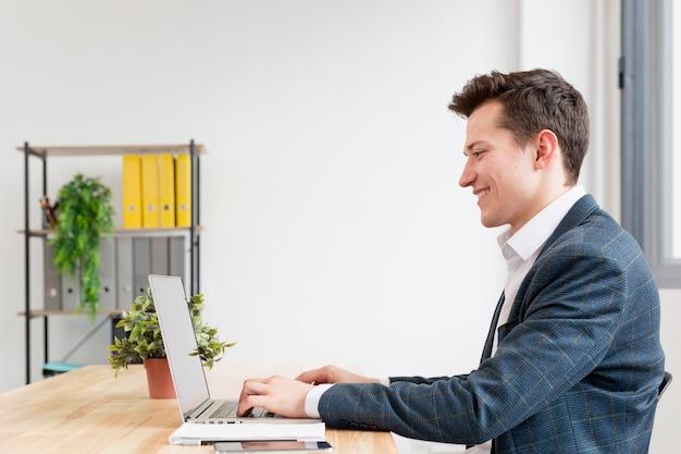 Widok Z Boku Dorosły Mężczyzna Pracuje Na Laptopie Darmowe Zdjęcia