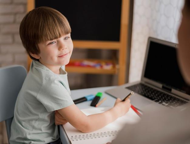 Widok Z Boku Dziecka Uczącego Się W Domu Z Opiekunem Darmowe Zdjęcia