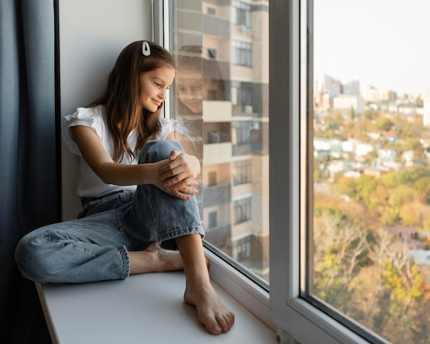 Widok Z Boku Dziewczyna Patrząc Przez Okno W Domu Darmowe Zdjęcia
