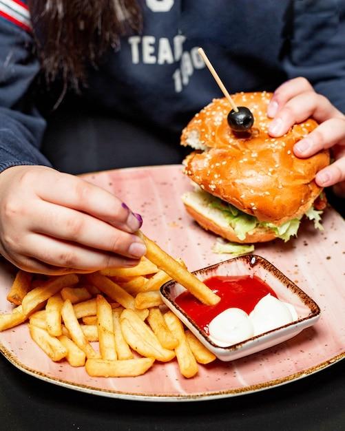 Widok Z Boku Dziewczyny Jedzącej Burgera Z Kurczaka Podawane Z Frytkami I Sosami Przy Stole Darmowe Zdjęcia
