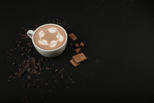 Widok Z Boku Filiżanka Cappuccino Z Czekoladą Na Czarnym Stole Darmowe Zdjęcia