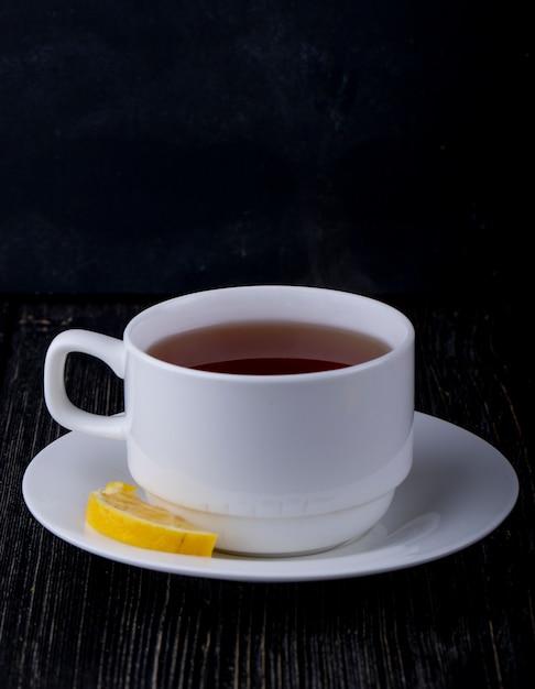 Widok Z Boku Filiżankę Herbaty Z Plasterkiem Cytryny Na Czarno Darmowe Zdjęcia