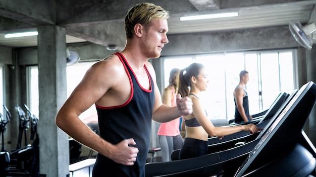 Widok z boku grupa młodych atrakcyjnych ludzi sportowych na bieżni. sportowiec na bieżni Premium Zdjęcia
