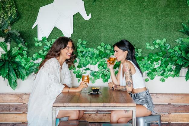 Widok Z Boku Kobiet Pijących Piwo Przy Stole Darmowe Zdjęcia