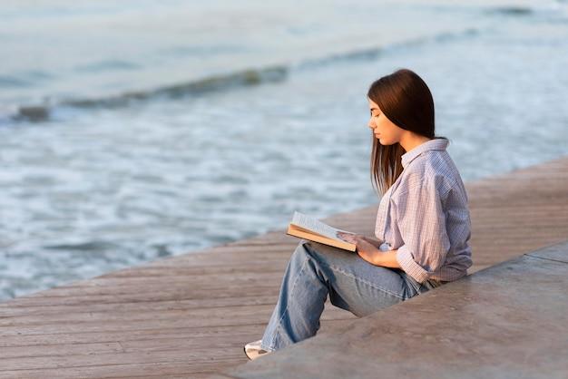 Widok Z Boku Kobieta Czytająca Książkę Na Plaży Premium Zdjęcia
