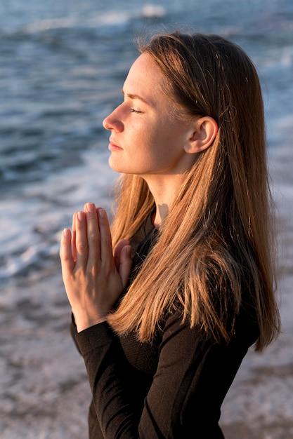 Widok Z Boku Kobieta Medytuje Na Plaży Darmowe Zdjęcia