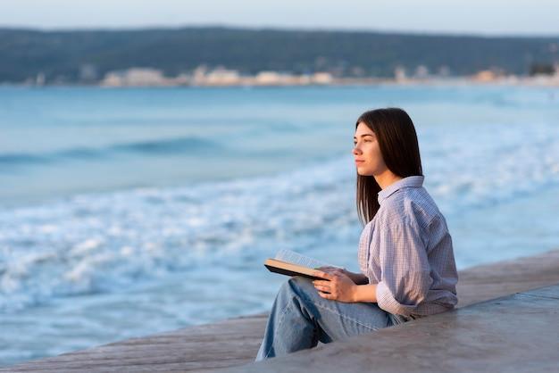 Widok Z Boku Kobieta Trzyma Książkę Z Miejsca Na Kopię Premium Zdjęcia