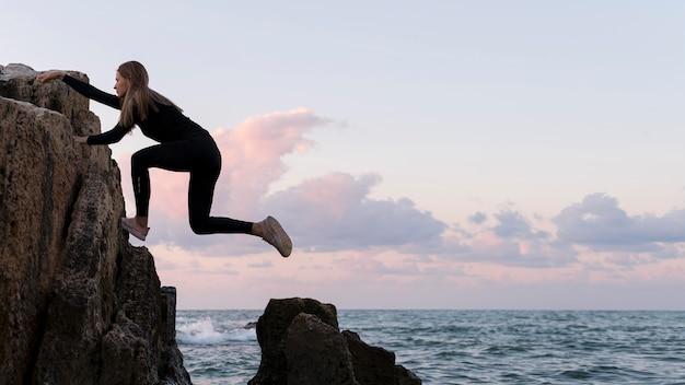 Widok Z Boku Kobieta Wspinaczka Na Wybrzeżu Darmowe Zdjęcia
