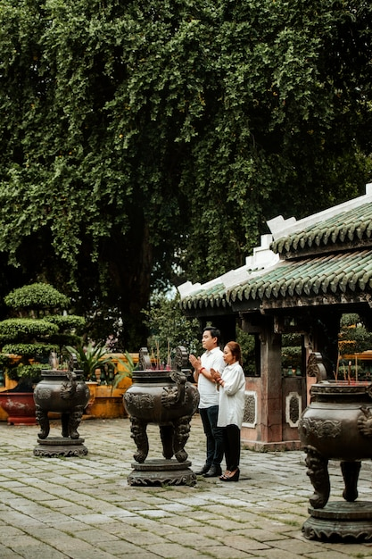 Widok Z Boku Kobiety I Mężczyzny Modlących Się W świątyni Z Płonącym Kadzidłem Darmowe Zdjęcia
