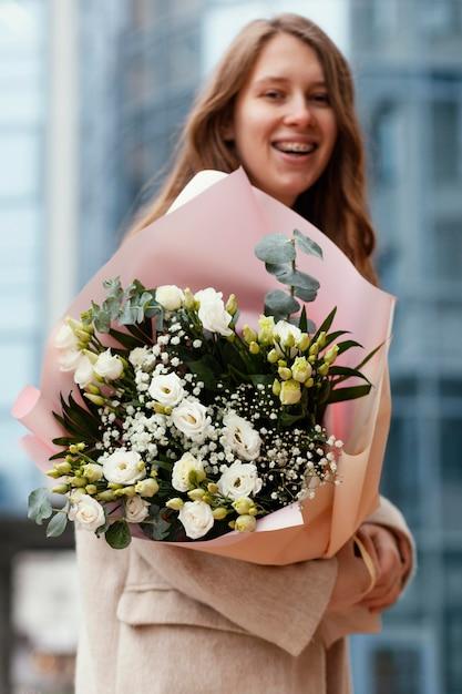 Widok Z Boku Kobiety Trzymającej Bukiet Kwiatów Na Zewnątrz Premium Zdjęcia