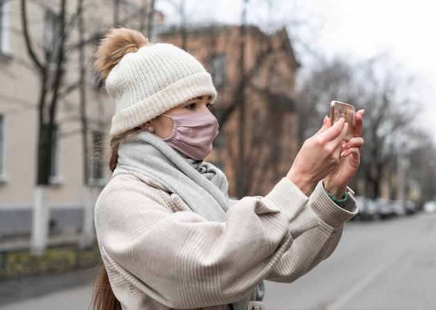 Widok Z Boku Kobiety Z Maską Medyczną O Rozmowie Wideo Na Zewnątrz Darmowe Zdjęcia