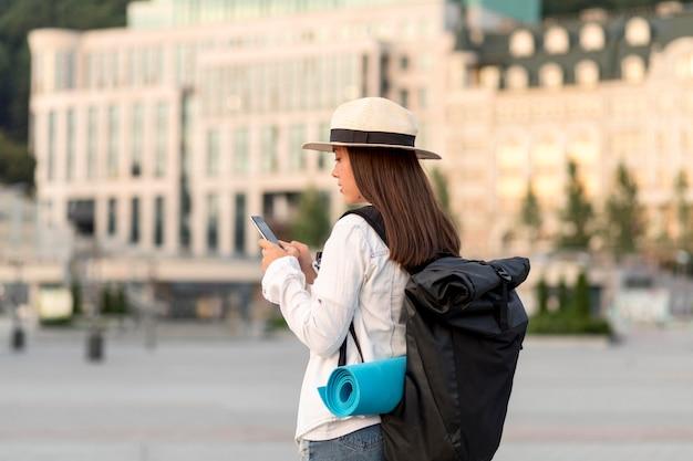 Widok Z Boku Kobiety Z Smartphone W Podróży Z Plecakiem Darmowe Zdjęcia