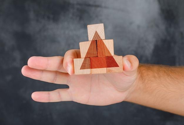 Widok Z Boku Koncepcji Strategii Biznesowej. Ręka Trzyma Piramidę Z Drewnianego Bloku. Darmowe Zdjęcia