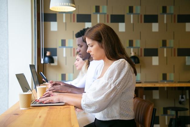 Widok Z Boku Ludzi Pracujących Na Laptopach I Siedzących Przy Stole W Pobliżu Okna Darmowe Zdjęcia
