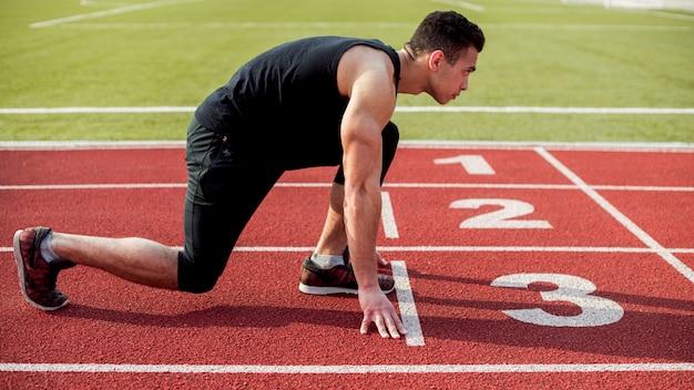 Widok Z Boku Męskiego Biegacza Sprinter Przygotowuje Się Do Rozpoczęcia Wyścigu Darmowe Zdjęcia