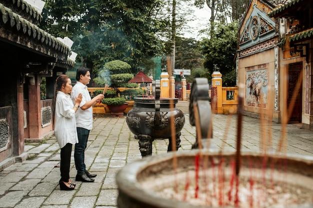 Widok Z Boku Mężczyzny I Kobiety Modlących Się W świątyni Z Płonącym Kadzidłem Darmowe Zdjęcia