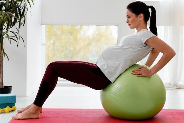 Widok Z Boku Młoda Kobieta W Ciąży ćwiczenia Na Piłce Fitness Darmowe Zdjęcia