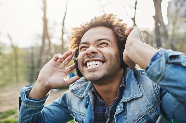 Widok Z Boku Na Zewnątrz Portret Podekscytowanego Szczęśliwego Afrykańskiego Mężczyzny Z Fryzurą Afro, Trzymającego Słuchawki, Słuchając Muzyki I Uśmiechając Się Szeroko, Zdumiony Tym, Co Słyszy. Darmowe Zdjęcia