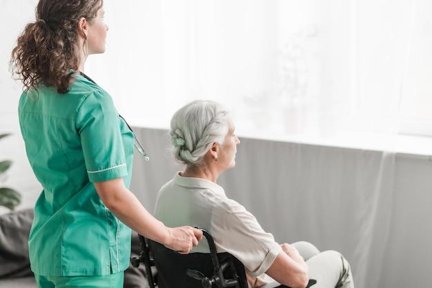 Widok z boku pielęgniarki pchania niepełnosprawnych pacjenta na wózku inwalidzkim Darmowe Zdjęcia