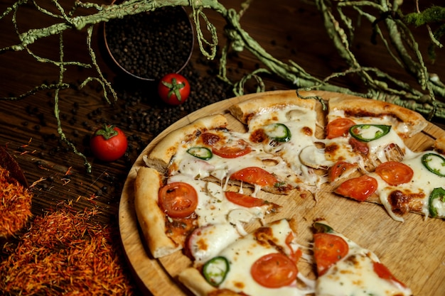 Widok Z Boku Pizza Na Stojaku Z Pomidorami I Czarnym Pieprzem Darmowe Zdjęcia