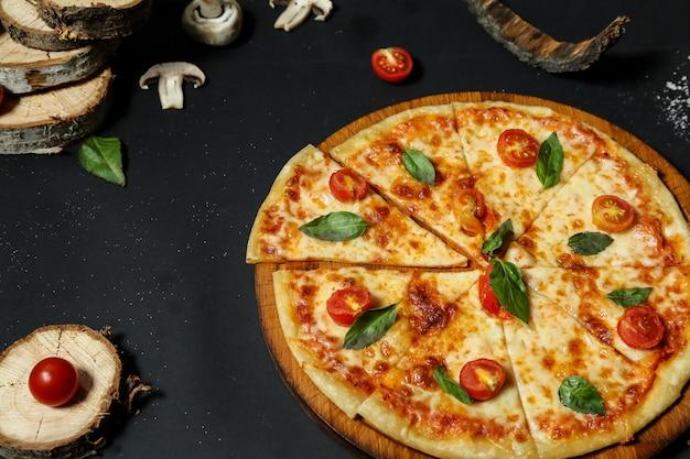 Widok Z Boku Pizza Na Tacy Z Pomidorami I Grzybami Na Czarnym Stole Darmowe Zdjęcia