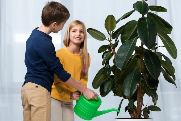 Widok Z Boku Podlewanie Kwiatów Dla Dzieci Razem Darmowe Zdjęcia