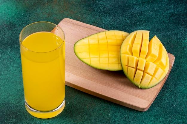 Widok Z Boku Pokrojone Mango Na Tablicy Ze Szklanką Soku Pomarańczowego Na Zielono Darmowe Zdjęcia