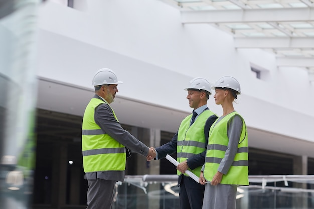 Widok Z Boku Portret Uśmiechniętych Ludzi Biznesu, ściskając Ręce Po Transakcji Inwestycyjnej Na Budowie, Premium Zdjęcia
