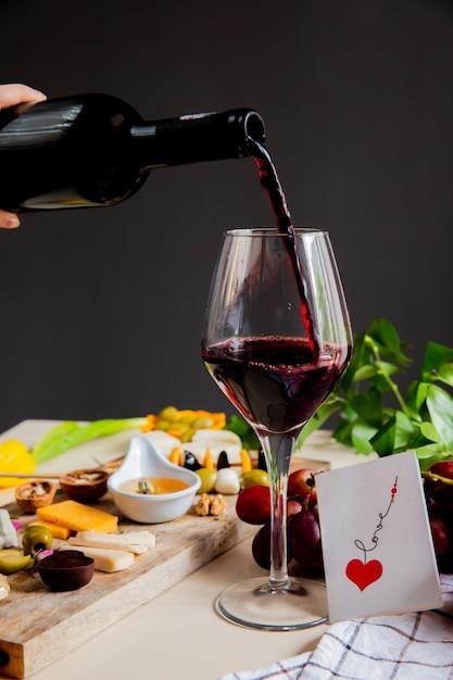 Widok Z Boku Ręki Kobiety Wlewając Czerwone Wino Do Szklanych I Serowych Oliwek Winogron I Miłości Karty Na Białej Powierzchni I Czarnej ścianie Darmowe Zdjęcia