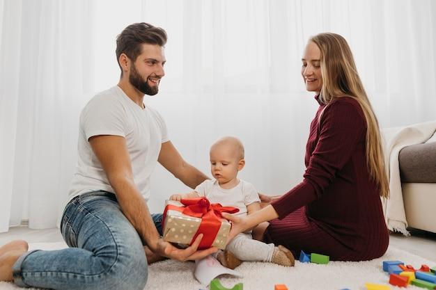 Widok Z Boku Rodziców W Domu Z Dzieckiem I Prezentem Darmowe Zdjęcia